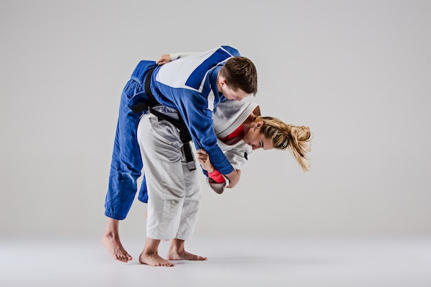Двое бойцов дзюдоистов позируют на сером Бесплатные Фотографии