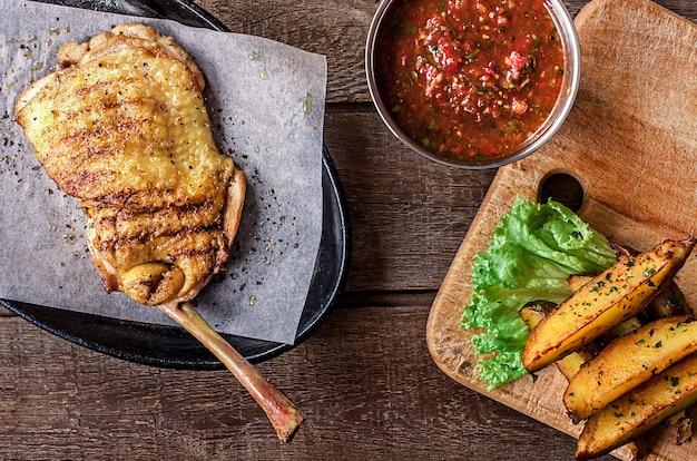 Жареное куриное мясо на кости, картофельные дольки, салат Бесплатные Фотографии