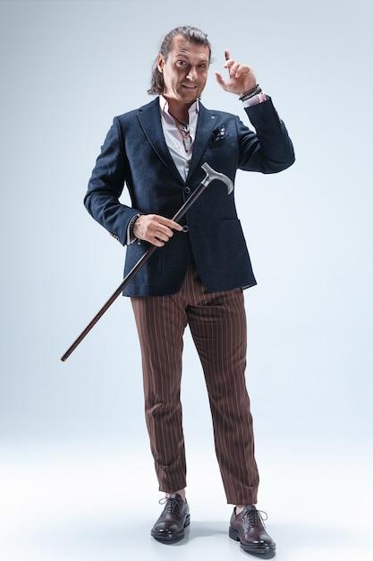 Зрелый мужчина в костюме с тростью. Бесплатные Фотографии