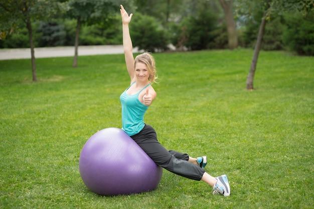 Молодая счастливая женщина с шариком фитнеса, напольным Бесплатные Фотографии