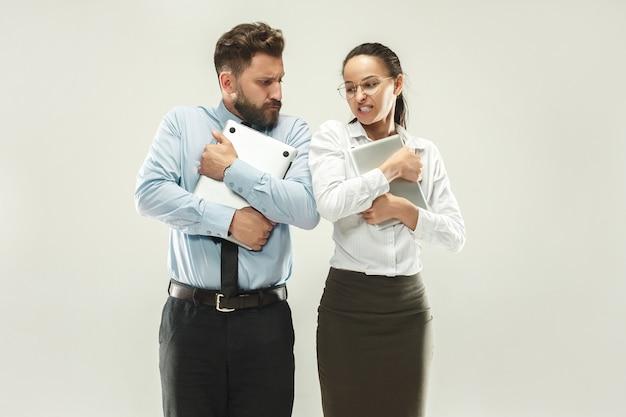 怒ったボス。男と彼の秘書が事務所に立っています。 無料写真