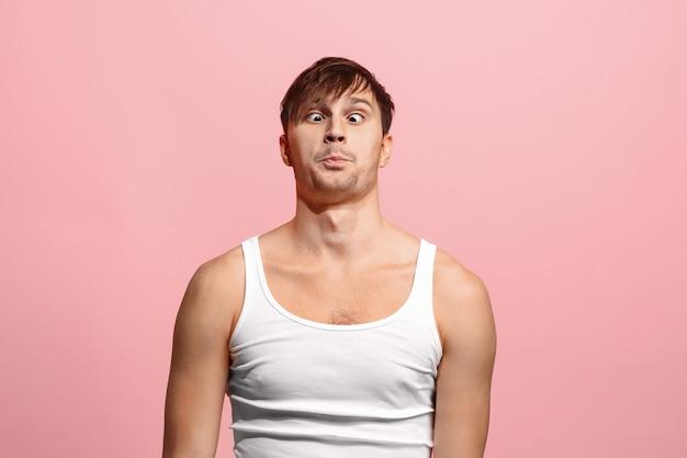 ピンクの壁に分離された奇妙な表情で斜視の目をした男 無料写真