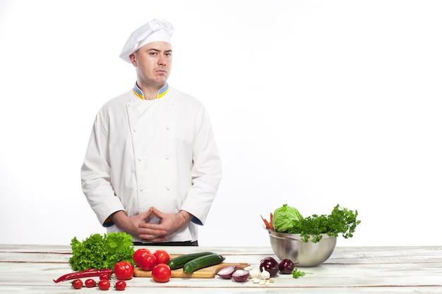 彼のキッチンで新鮮な野菜サラダを調理するシェフ 無料写真