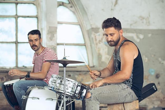 Повтор группы рок-музыки. электрогитарист и барабанщик за ударной установкой. Бесплатные Фотографии