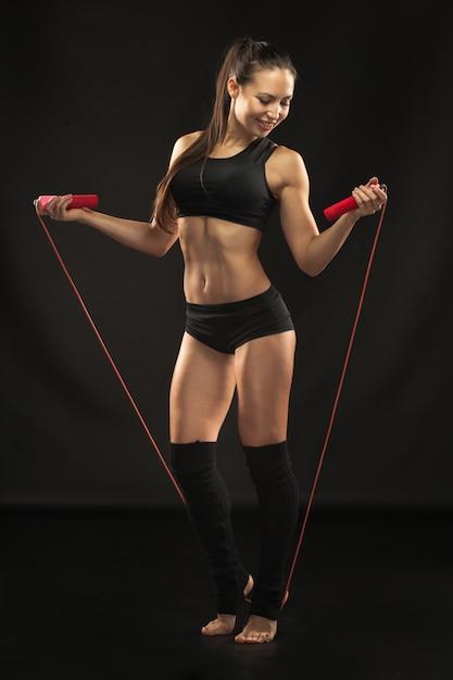 Мускулистые молодая женщина спортсмен со скакалкой на черном Бесплатные Фотографии