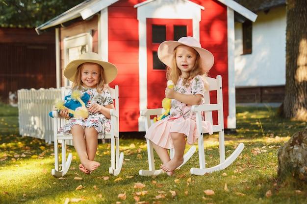 Милые маленькие белокурые девушки в шляпах сидя на поле с мягкими игрушками в лете. Бесплатные Фотографии