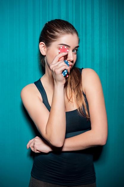 Молодая девушка держит фишки для покера на синем Бесплатные Фотографии