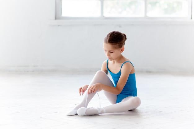 Красивая маленькая балерина в голубом платье надевает пуанты Бесплатные Фотографии