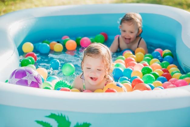 Две маленькие девочки играют с игрушками в надувном бассейне в солнечный летний день Бесплатные Фотографии