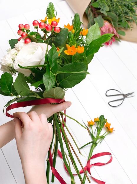 Женский флорист делает красивый букет в цветочном магазине Бесплатные Фотографии