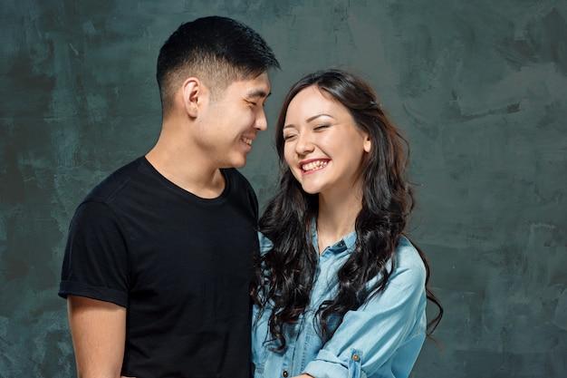 Улыбающаяся корейская пара на сером Бесплатные Фотографии