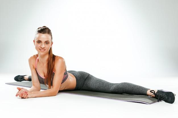 ジムでいくつかのストレッチ体操を行う美しいスリムなブルネット 無料写真
