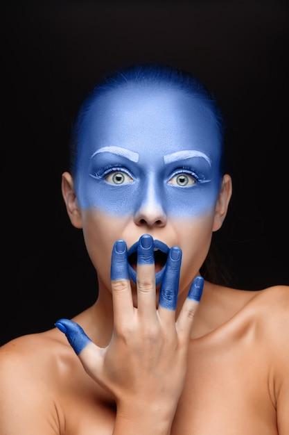 青いペンキで覆われたポーズの女性の肖像画 無料写真