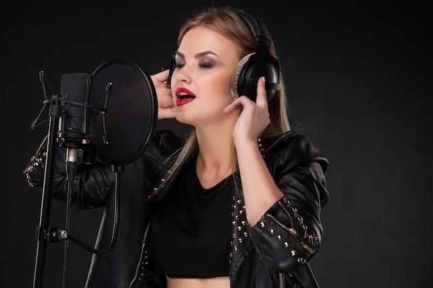 ヘッドフォンでマイクに向かって歌う美しい女性の肖像画 無料写真