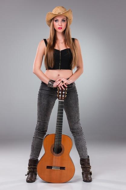 カウボーイハットとアコースティックギターで美しい少女。 無料写真