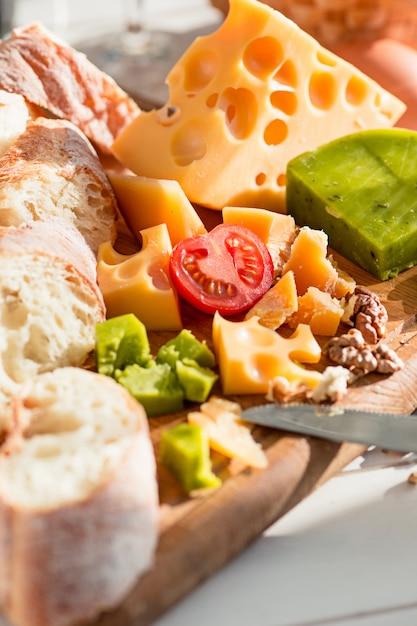 バゲットとチーズの木製のテーブル 無料写真
