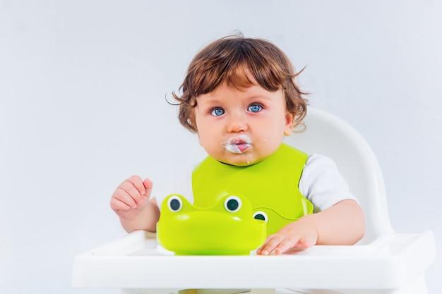 Счастливый ребёнок сидит и ест Бесплатные Фотографии