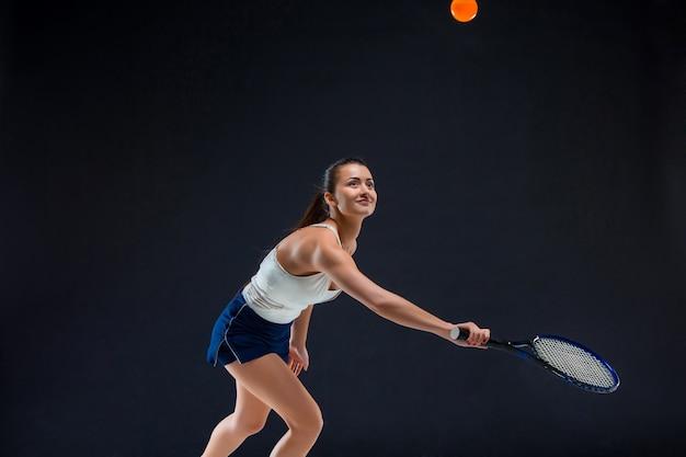暗い背景にラケットで美しい少女テニスプレーヤー 無料写真