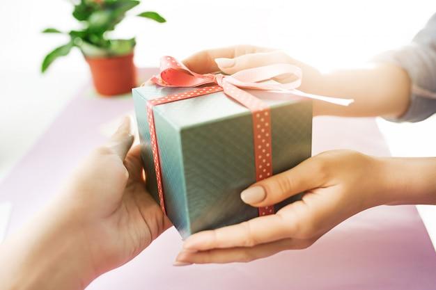 プレゼントを持っている女性の手のクローズアップ。トレンディなピンクのデスク。 無料写真