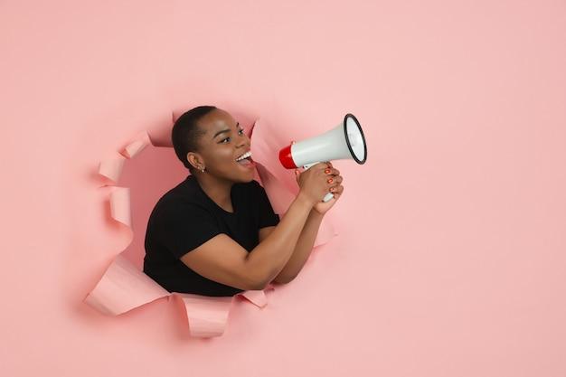 破れた画期的なピンクの背景に若い女性の肖像画 無料写真