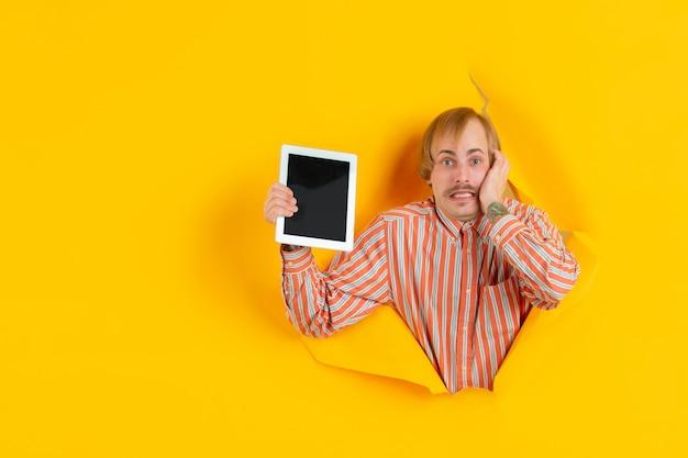 破れた画期的な黄色の背景に若い男の肖像 無料写真