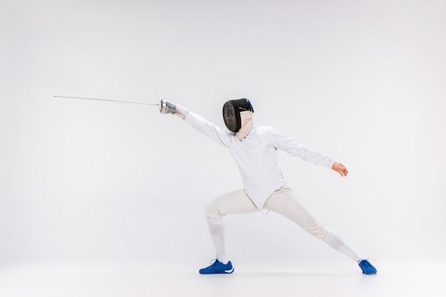 灰色に対して剣で練習するフェンシングスーツを着た男 無料写真