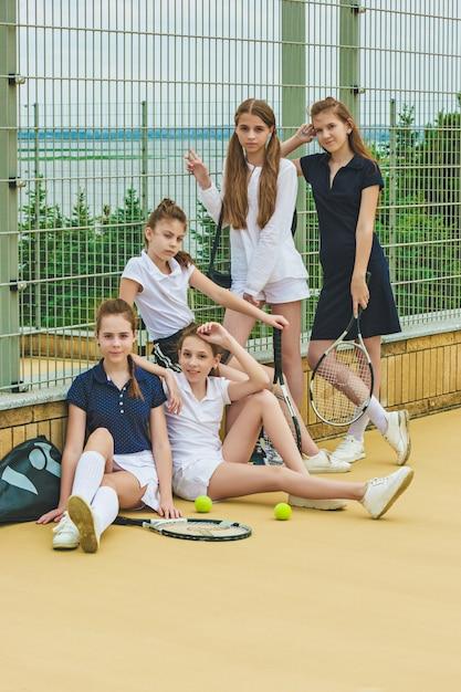 Портрет группы девушек как теннисистки с теннисной ракеткой на фоне зеленой травы открытого корта Бесплатные Фотографии