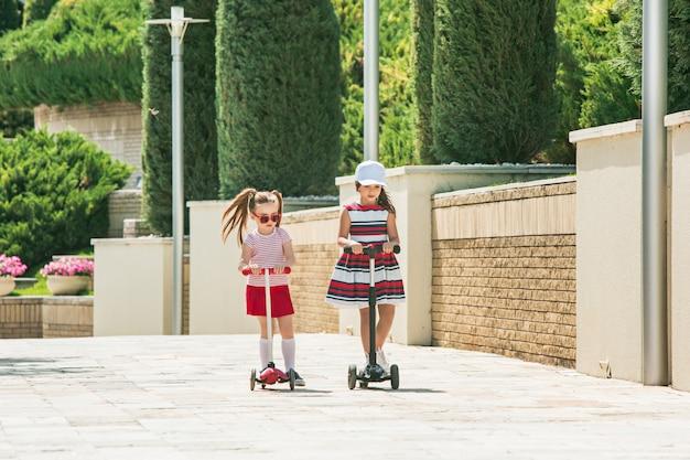 屋外のスクーターに乗る幼児の女の子。 無料写真