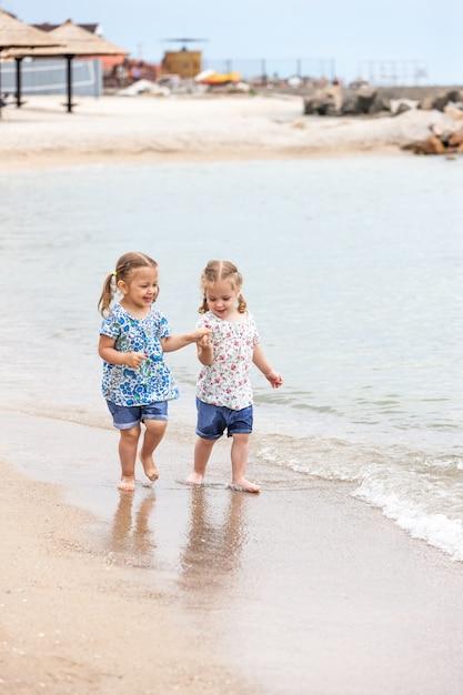 海のビーチで子供たち。海の水に沿って行く双子。 無料写真