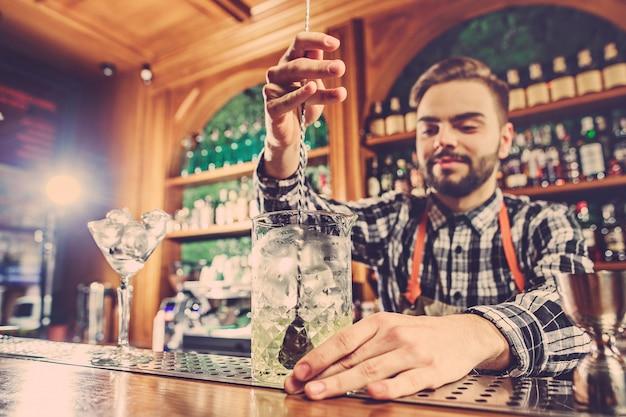 バーのバーカウンターでアルコールカクテルを作るバーマン 無料写真