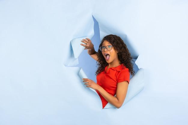 破れた青い紙の穴の背景、感情的で表現力豊かな陽気な若い女性のポーズ 無料写真