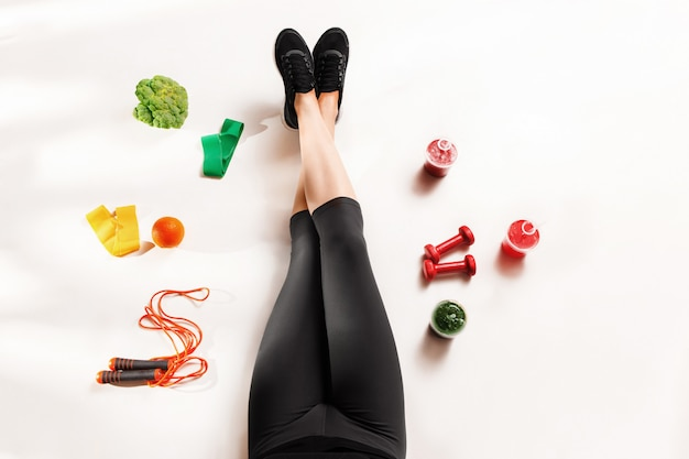 Спортивная девушка со здоровой пищей на полу Бесплатные Фотографии