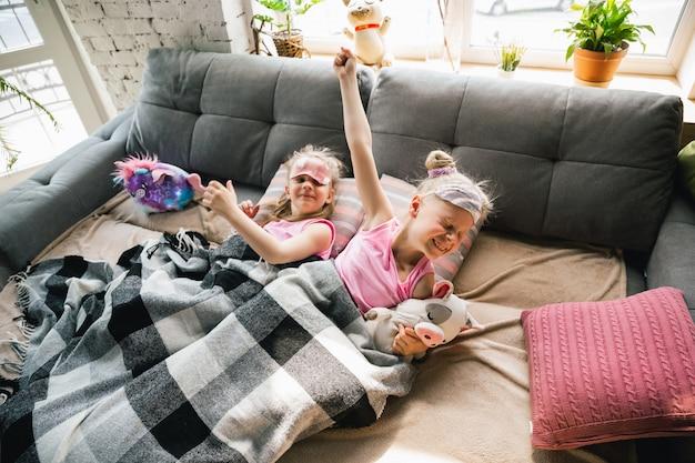 かわいいパジャマ、ホームスタイル、快適さで寝室で目覚める静かな女の子 無料写真