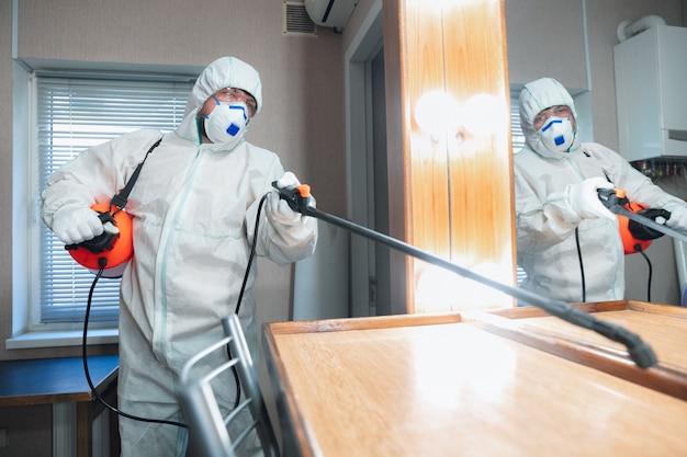 コロナウイルスパンデミック。保護スーツを着た消毒器とマスクが家またはオフィスに消毒剤をスプレーする 無料写真