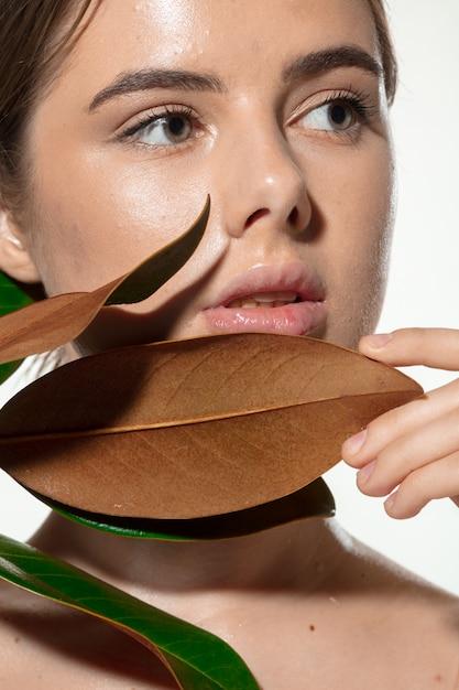 Вдохновленный. закройте вверх красивой молодой женщины с зелеными листьями на ее стороне над белизной. косметика и макияж, натуральные и эко-процедуры, уход за кожей Бесплатные Фотографии