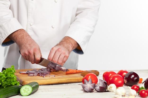 彼のキッチンでタマネギを切るシェフ 無料写真
