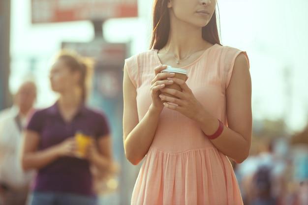 Красивые девушки держат бумажную кофейную чашку и наслаждаются прогулкой по городу Бесплатные Фотографии
