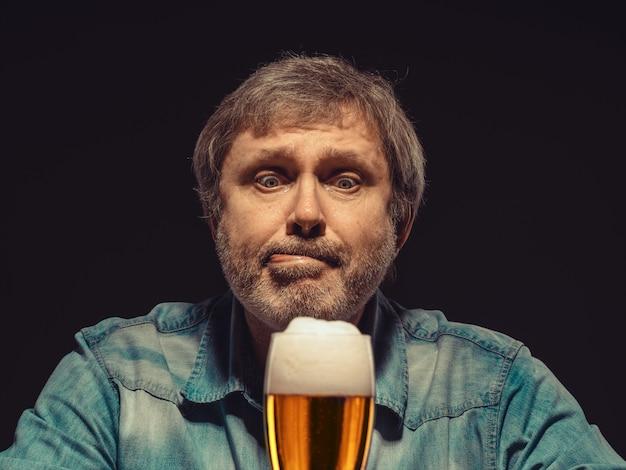 ビールのグラスとデニムシャツの魅惑の男 無料写真
