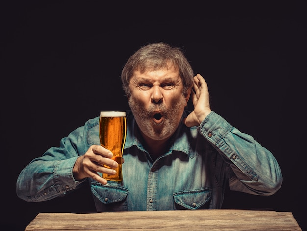 ビールのグラスで魅惑的で感情的なファン 無料写真