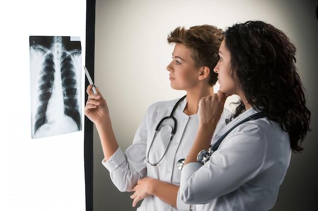 Два привлекательных молодых доктора, смотрящие на результаты рентгена Бесплатные Фотографии