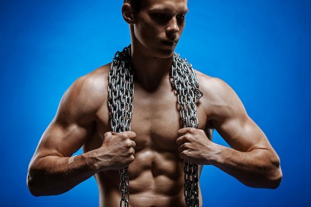 Мускулистый парень с цепями на плечах на фоне голубой стены Бесплатные Фотографии