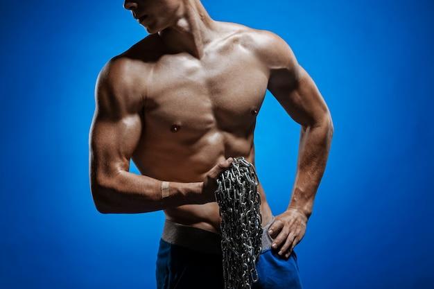青い壁に肩に鎖を持つ筋肉男 無料写真