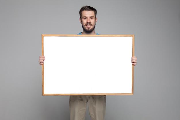 Улыбающийся человек показывает пустую доску Бесплатные Фотографии