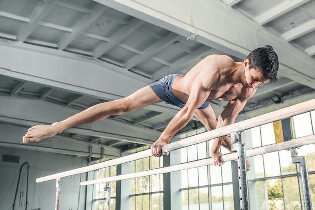 Мужской гимнаст выполняет стойку на руках на параллельных брусьях Бесплатные Фотографии