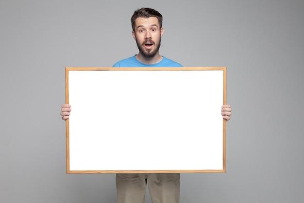 Удивленный человек показывая пустую белую доску Бесплатные Фотографии
