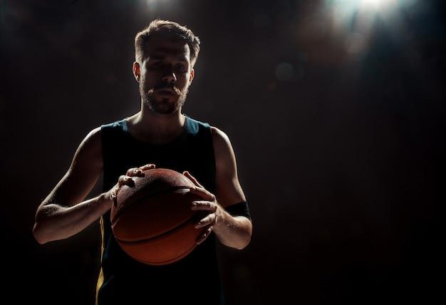 黒い壁にバスケットボールを保持しているバスケットボール選手のシルエットビュー 無料写真