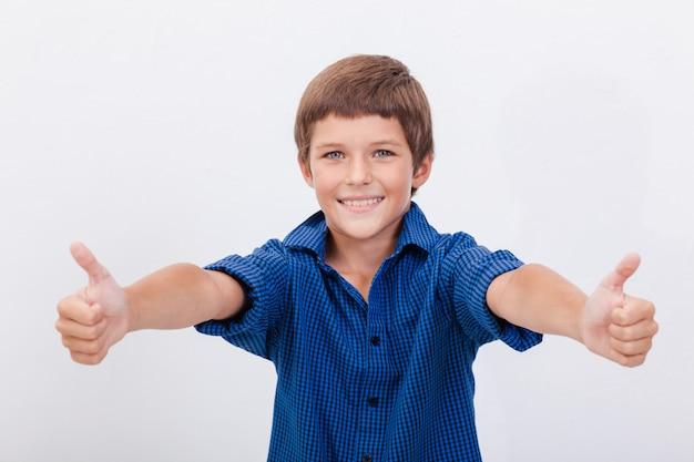 親指ジェスチャーを示す幸せな少年の肖像画 無料写真