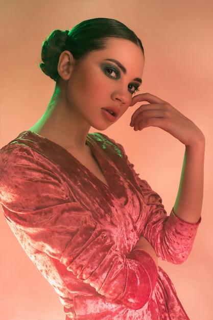 カラフルな明るいライトポーズでファッション性の高いモデルの女性 無料写真