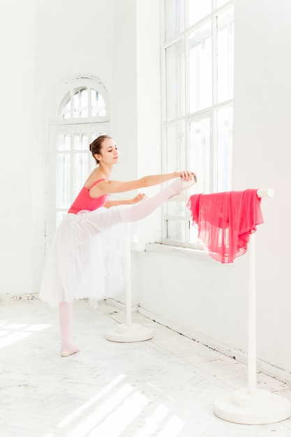 Балерина позирует в пуанты в белом деревянном павильоне Бесплатные Фотографии