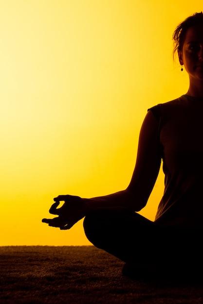 夕日の光の中でヨガの練習の女性 無料写真
